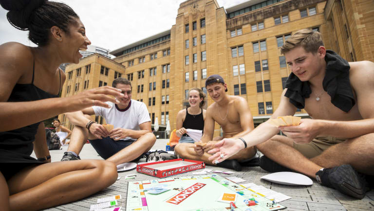 German backpackers get involved in a game of Monopoly in front of the MCA as they wait for the fireworks to start.