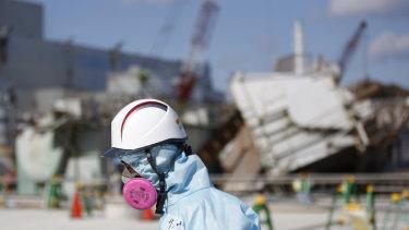 A TEPCO employee outside the No. 1 reactor building at the tsunami-crippled Fukushima Dai-ichi nuclear power plant.