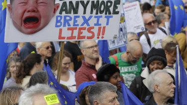 Anti-Brexit demonstrators carry placards and EU flags in London, Saturday