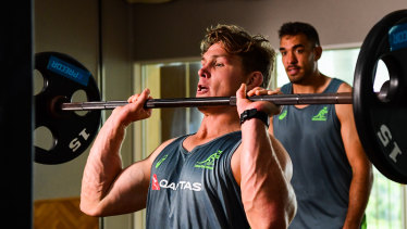 Rory Arnold looks on as Michael Hooper goes hard in the gym on Saturday in Odawara.