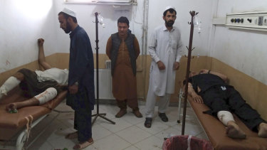 Injured men receive treatment following a deadly bombing at a mosque in Khost on Sunday.