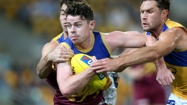Lachie Neale is tackled during the round 23 match between the Brisbane Lions and the West Coast Eagles at the Gabba.