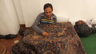 A darner repairs a rug.