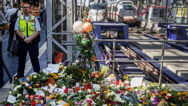Flowers and candles were placed near a track at the main train station in Frankfurt, Germany.