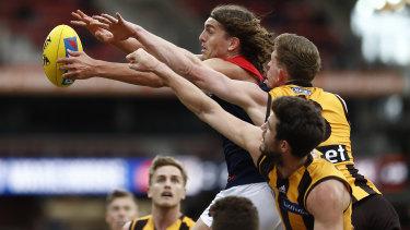 Pole position: Melbourne's Luke Jackson fends off a pair of Hawks.
