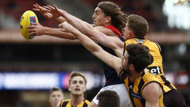Melbourne's Luke Jackson fends off a pair of Hawks.