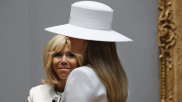 French First Lady Brigitte Macron, left, smiles at her counterpart Melania Trump as they tour the National Gallery of Art, in Washington.
