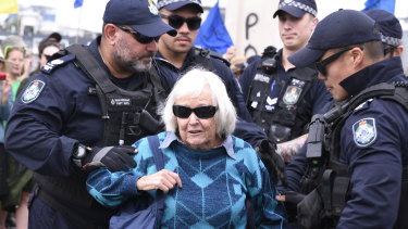 An Extinction Rebellion activist is arrested on the William Jolly Bridge on Friday.