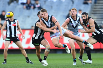 Port's Ollie Wines handballs as he is tackled by Taylor Adams.