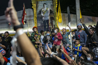 A painting of Thailand King Maha Vajiralongkorn is seen as protesters hold the three finger salute during a rally last week.
