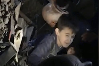 People work to free a young boy from a collapsed building in the coastal town of Durres.