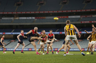 Max Gawn gets a kick away for the Demons in their draw with Hawthorn at a crowdless MCG.