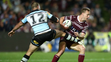 Leg over: Wade Graham tries an unusual approach to stopping Daly Cherry-Evans.