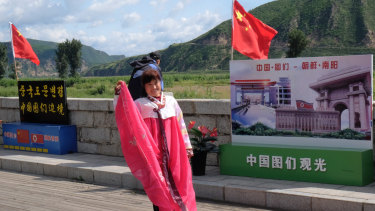 A Chinese tourist puts on a traditional Korean costume to take pictures on the riverfront promenade in Tumen, China.