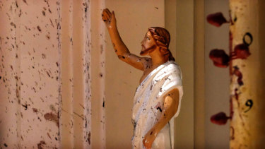 Blood stains the wall and a statue of Jesus Christ after a blast ripped through St Sebastian's Church in Negombo, north of Colombo, on Sunday.