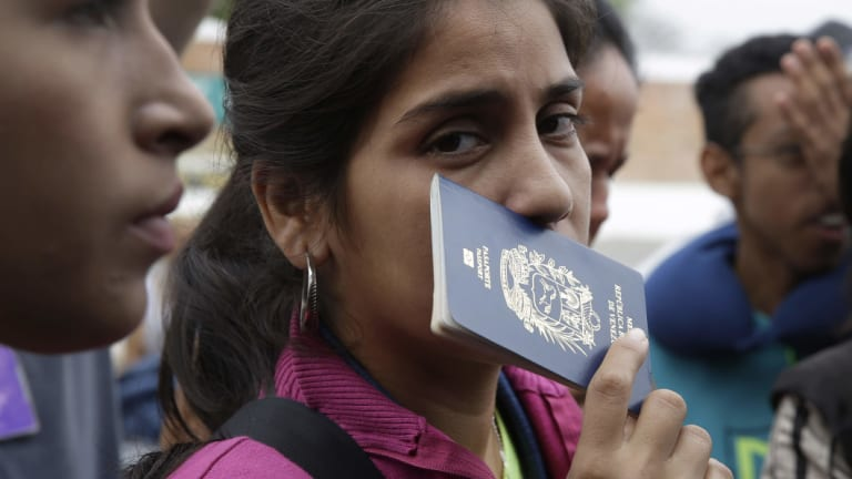 A Venezuelan migrant holds her passport while wait in line to take a bus to continue their travel in Tumbes, Peru.