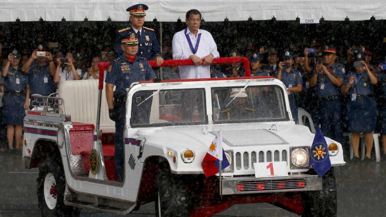 President Rodrigo Duterte, right, reviews a police  gathering under a sudden downpour last week.