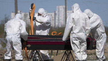 Grave diggers wearing protective suits prepare to bury a COVID-19 victim in a special section of a cemetery in Kolpino, outside St Petersburg, Russia.