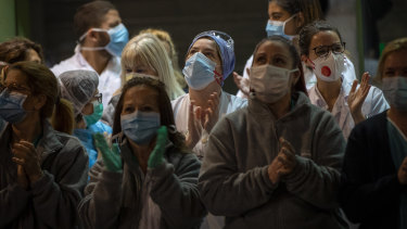 Health workers react as people applaud from their houses in support of the medical staff that are working on the COVID-19 virus outbreak at the main gate of the Hospital Clinic in Barcelona, Spain.
