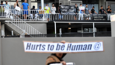 A refugee supporter walks by holding a sign as asylum seekers who are being held in detention at an inner city motel are seen protesting in Brisbane.