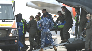 A survivor of the Whaakaari volcanic eruption in New Zealand is removed on a stretcher from a RAAF Hercules at Sydney Airport on Thursday.