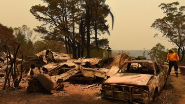 RFS assessment officer Adam Small inspects a home burnt out during the Green Wattle Creek fire south-west of Sydney.