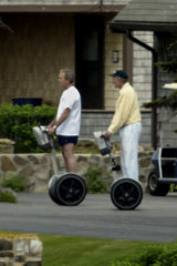 Then US President George W. Bush (left) and his father former President George Bush ride Segways in the front driveway of the Bush family summer home in 2003.