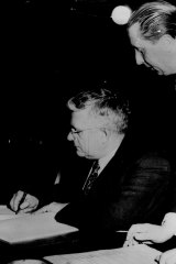 Dr. Herbert V. Evatt, President of the United Nations General Assembly, signs - on behalf of his country - the UN convention outlawing genocide.