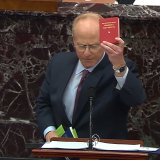David Schoen, an attorney for former President Donald Trump brandishes Mao Zedong's Little Red Book as he speaks.