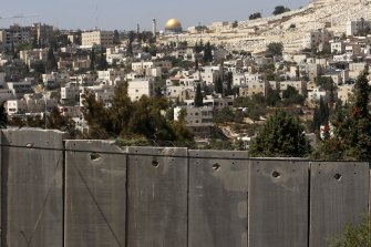 The Dome of the Rock, located on the compound known to Muslims as al-Haram al-Sharif (Noble Sanctuary) and to Jews as Temple Mount in Jerusalem's Old City, is seen in the background above the controversial Israeli barrier in the West Bank village of Abu Dis in September 2009.