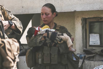 In this August 20, 2021, image, Sgt Nicole Gee calms an infant during the evacuation at Hamid Karzai International Airport in Kabul. Gee was later killed in a bombing outside the airport.