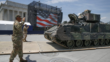 Army soldiers with the 3rd Infantry Division, 1st Battalion, 64th Armored Regiment, move a Bradley Fighting Vehicle into place by the Lincoln Memorial.