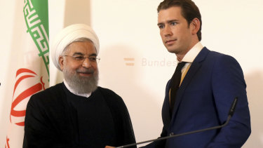Hassan Rouhani shakes hand with Austrian Chancellor Sebastian Kurz at the federal chancellery in Vienna.