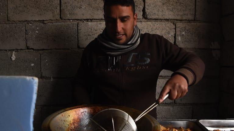 A man fries falafel and chips in hot oil in Daquq IDP camp in Kirkuk, Iraq.