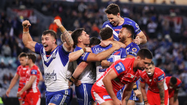 Bulldogs players celebrate a try in the win over the Dragons.