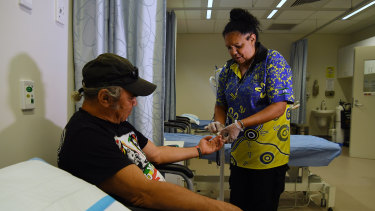 Health worker Vicky Connolly checks the sugar levels of patient Rick McEwan at the Tharawal Aboriginal Corporation Aboriginal Medical Service in Airds.