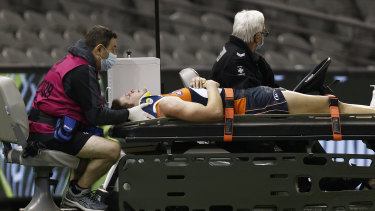 Jacob Hopper of the Giants is stretchered off the ground.