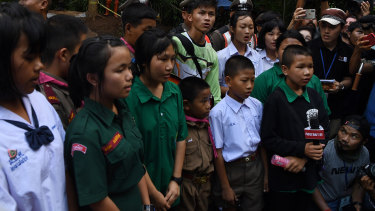 Friends and classmates of the trapped boys in Tham Luang cave sing for them.