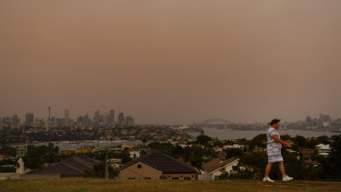 Dust fills the air as a woman walks at Dudley Page Reserve in Dover Heights on Wednesday morning.