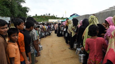 Rohingya refugees queue for a meal provided by a Turkish aid agency at a food distribution site in Shofiullah Kata Camp in Bangladesh.