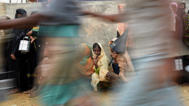Rohingya refugee women wait in line as men run past for a meal provided by a Turkish aid agency.