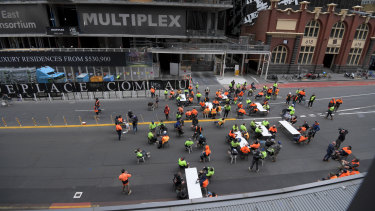 Construction workers using a street in Melbourne's CBD as a tearoom on Friday.