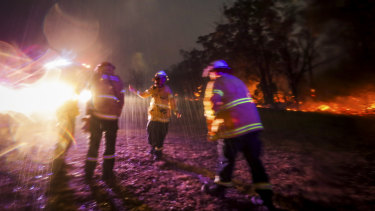 Firefighter Mikaela Kremer dances to celebrate the sudden burst of rain over  Glenbrook-Lapstone bringing a welcome relief from the fires on Saturday, December 21, 2019.