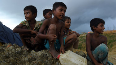 Rohingya children sit on the side of a road in Kutupalong camp, part of the largest refugee camp in the world, home to over 400,000 of 900,000 Rohingya refugees who fled Myanmar in August 2017. Cox's Bazar, Bangladesh.