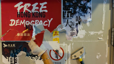 A pro-China supporter cleans up a Lennon walls of anti-government posters and memo notes outside Yeun Long MTR station on Saturday.
