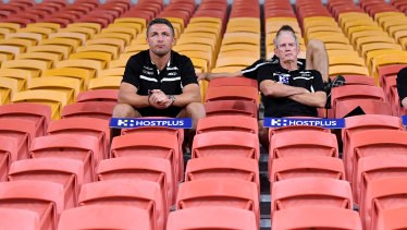 Sam Burgess, left, and Rabbitohs coach Wayne Bennett watching the game unfold from behind the goal posts.