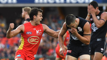 Blue Sun day: Carlton players react after last-gasp snap by Gold Coast's Jack Bowes (left).
