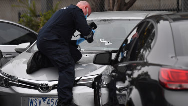 Police examine bullet holes after a junior officer fired shots into the shoulder of a man at Tullamarine early on Friday.