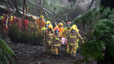 Emergency crews rescue a woman in Olinda on Thursday.