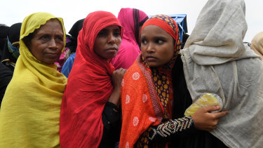 A Rohingya woman holds her ration cards in a plastic cover to protect them from the rain whilst in queuing for food.